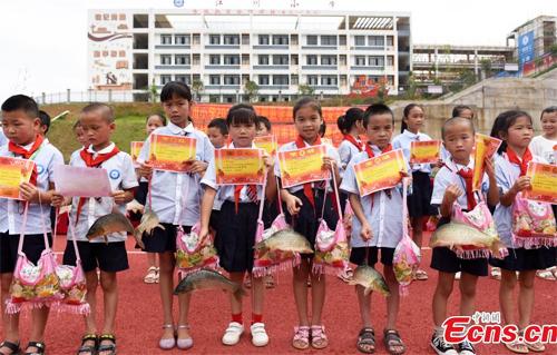 Học sinh trường tiểu học Jiangchuan được tặng phần thưởng học sinh giỏi bao gồm cá chép sống, thạch và bằng khen. Ảnh: Ecns.