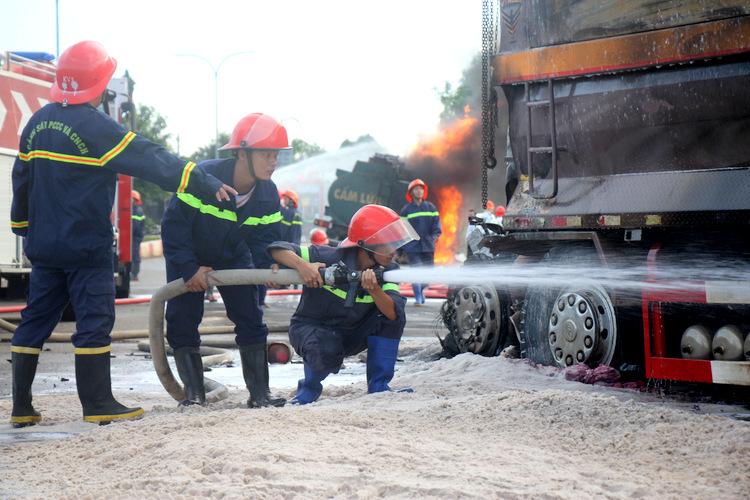 Cảnh sát chia hai tóp dập đám cháy xe bồn và liên tục phun nước dập lửa xe ben cháy âm ỉ. Ảnh: Nguyễn Khoa.