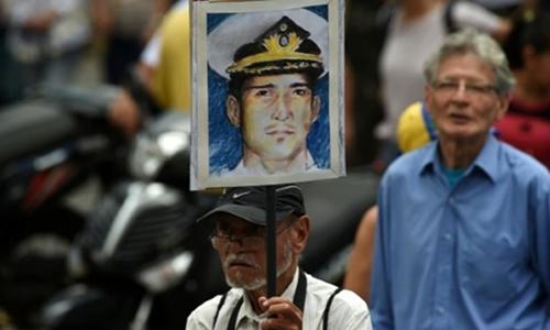 Một người đàn ông ở Caracas giơ chân dung của đại tá Rafael Acosta, người mà gia đình và Mỹ cho rằng đã bị quân đội Venezuela tra tấn tới chết trong tù. Ảnh: AFP.