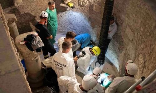 Chuyên gia pháp y mở khoang hầm hài cốt ở bên cạnh nghĩa trang Teutonic ngày 20/7. Ảnh: Reuters