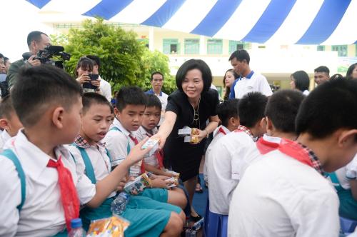 Bà Bùi Thị Hương trao tận tay các hộp sữa thơm ngon và bổ dưỡng đến các em học sinh tham dự chương trình.