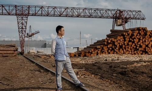 Quản đốc Wang Yiren đứng trước một đống gỗ tại xưởng ở Kansk trước khi chúng được chuyển về Trung Quốc. Ảnh: New York Times.