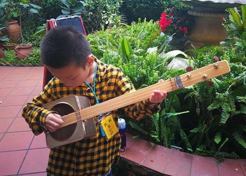 Chen Muyuan (8 tuổi, thành viên ban nhạc Tái chế) tập chơi đàn guitar được tái chế từ vỏ hộp bánh, bìa các tông. Ảnh: China Daily.