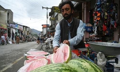 Người bán hàng rong bọc dưa hấu trong túi nilon trên một con phố ở Chitral hôm 17/5. Ảnh: AFP.