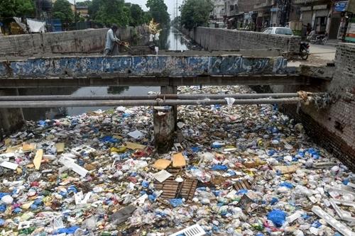 Một người bán hàng đẩy xe chởngô qua một con kênh đầy túi nilon và rác ở Lahore, thủ phủ tỉnh Punjab, thành phố đông dân thứ hai Pakistan,hôm 31/7. Ảnh: AFP.