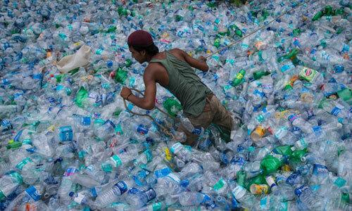 Một thanh niên trong biển chai nhựa ở Pakistan. Ảnh: Reuters.