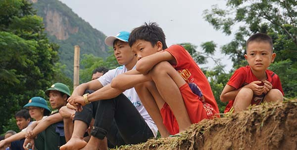 Người thân ngồi trên bờ sông Luồng ngóng chờ tin tức tìm kiếm người mất tích từ đội cứu hộ.Ảnh: Lê Hoàng.