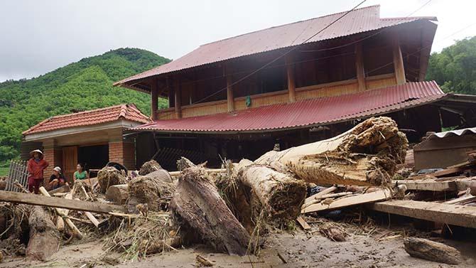 Những căn nhà kiên cố nhất ở Sa Ná cũng hư hỏng, cây cối ngổn ngang khắp ngõ ngách. Ảnh: Lê Hoàng.