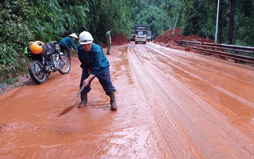 Lực lượng cứu hộ dọn bùn đất tạiđiểm sạt lở. Ảnh: Hoài Thanh.