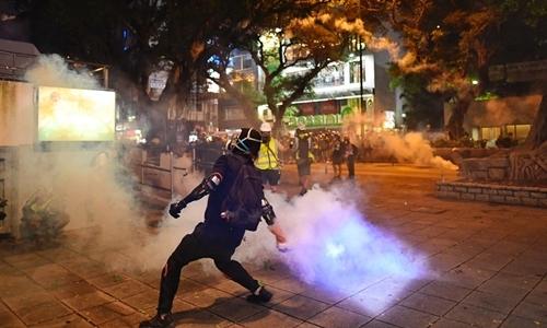 Người biểu tình Hong Kong ném hơi cay vào cảnh sát ở quận Sham Shui Po, Hong Kong, hôm 11/8. Ảnh: AFP.
