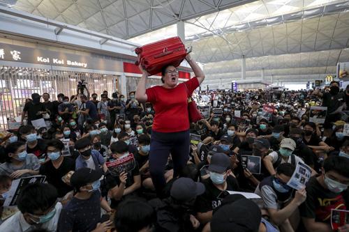 Nữ hành khách (áo đỏ) chật vật tìm lối đi giữa đám đông biểu tình ở sân bay Hong Kong chiều nay. Ảnh: SCMP.