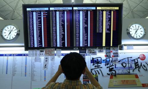 Một hành khách chụp danh sách chuyến bay bị hủy tối 12/8. Ảnh: SCMP.