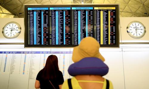 Một hành khách chụp danh sách chuyến bay bị hủy sáng 13/8. Ảnh: SCMP.