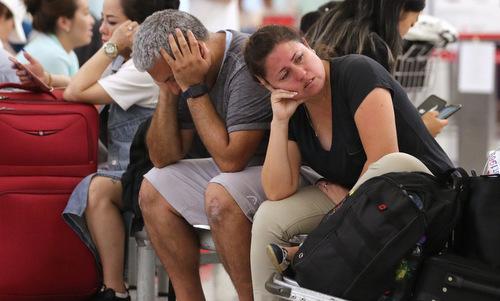 Hành khách ngồi chờ tại sân bay Hong Kong tối 12/8. Ảnh: SCMP.