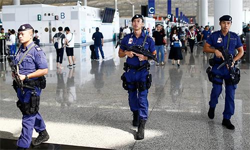 Cảnh sát vũ trang tuần tra trong sân bay quốc tế Hong Kong sáng 14/8. Ảnh: Reuters.
