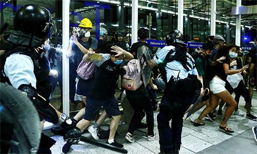 Cảnh sát chống bạo động trấn áp người biểu tình tại sân bay quốc tế Hong Kong tối 13/8. Ảnh: Reuters.