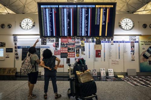 Hành khách đứng trước bảng hiển thị các chuyến bay bị hủy ở sân bay quốc tế Hong Kong hôm 12/8. Ảnh: AFP.