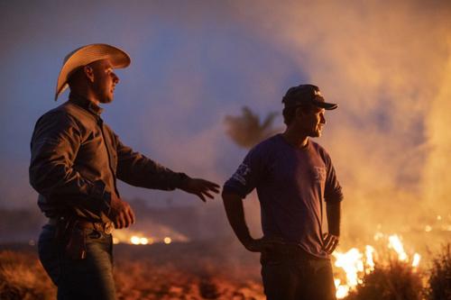 Hai công nhân ở bang Mato Grosso, phía nam lưu vực sông Amazon ở Brazil, nhìn đám cháy lan đến trang trại họ làm việc hôm 23/8. Ảnh: AFP.