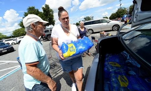 Sheila Guerrabê nước đóng chai vào cốp xe ở bãi đỗ siêu thị Walmart ở Orlando, Florida hôm 29/8. Ảnh: AFP.