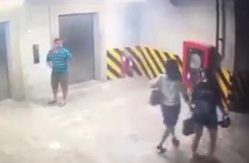 Hành động của Thành (áo kẻ xanh đứng cạnh thang máy) bị camera ghi lại.