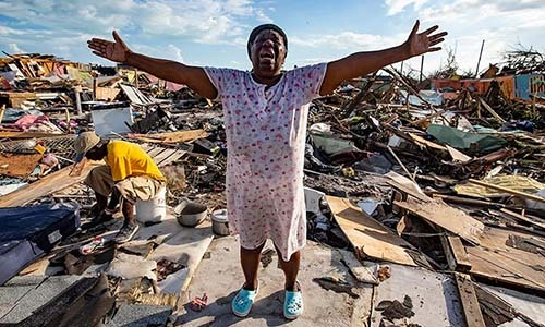 Cư dân Bahamas đứng trên đống đổ nát sau bão Dorian. Ảnh: AP.