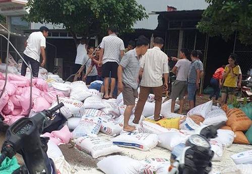 Người dân giúp tài xế thu gom năm tấn gạo bị rơi ra ngoài. Ảnh: Quang Hà