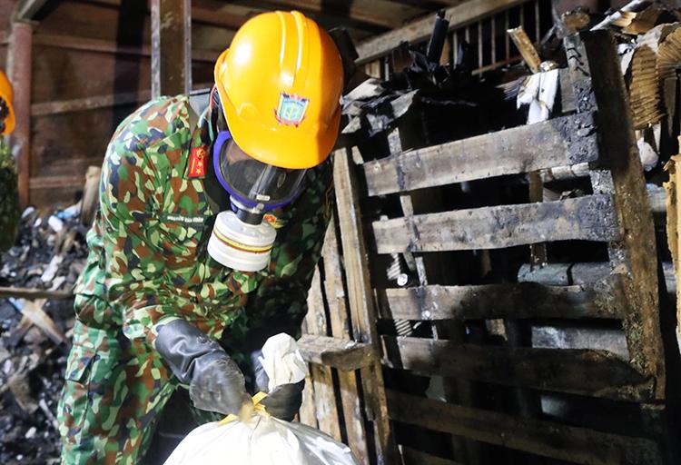 Bộ đội Hoá học thu gom phế thải tại hiện trường vụ cháy kho Rạng Đông sáng 12/9. Ảnh: Ngọc Thành.
