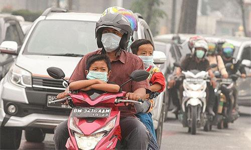 Một gia đình ở Pekanbaru, tỉnh Riau của Indonesia đeo khẩu trang khi di chuyển trong làn khói mù dày đặc vì cháy rừng hôm 15/9. Ảnh: Straits Times.