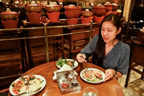 Diane Piroon, người ăn chay trường, thử món pad kra phao trong nhà hàng ở Bangkok hôm 4/9. Ảnh: AFP