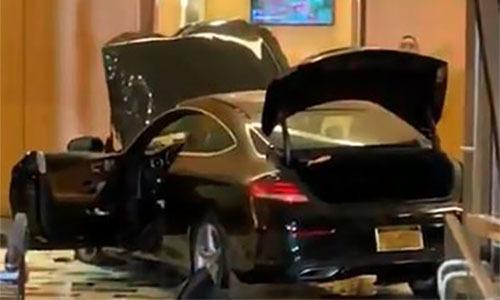 Chiếc xe nằm ở giữa sảnh tòa nhà và nắp capo bị bật lên sau khi đâm qua cửa kính tối 17/9. Ảnh: Twitter/Tony Aiello.