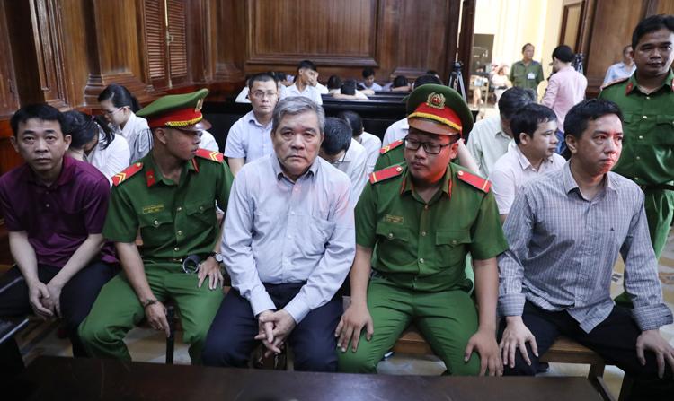 Các bị cáo Phạm Văn Thông (giữa) - người được VN Pharma thuê viết hồ sơ thuốc để làm thủ tục nhập khẩu. Ảnh: Hữu Khoa..