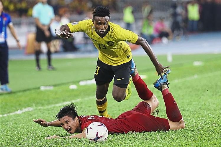 Sumareh tranh chấp với Đoàn Văn Hậu khi Maylaysia và Việt Nam gặp nhau tại AFF Cup 2018 trên sân Bukit Jalil. Ảnh: AP.
