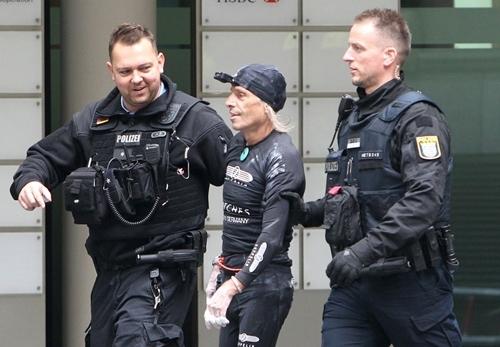 Alain Robert (giữa) bị cảnh sát Đức giải đi ở Frankfurt ngày 28/9. Ảnh: AFP.