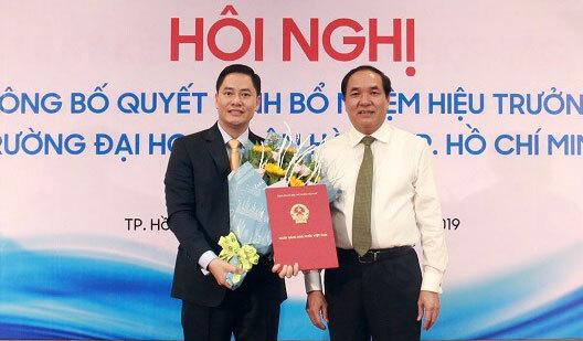 Ông Bùi Hữu Toàn (trái) nhận quyết định bổ nhiệm Hiệu trưởng. Ảnh: Đại học Ngân hàng TP HCM.
