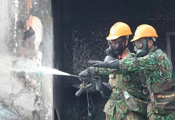 Bộ đội Hóa học phun tẩy, khử độc ở những bức tường cuối cùng của nhà kho Rạng Đông, chiều 5/10. Ảnh: Hiếu Duy