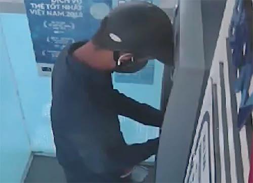 Người bịt mặt thực hiện hành vi đánh cắp dữ liệu tại cây ATM. Ảnh: Cắt từ video
