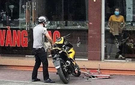 Ôm ba lô đựng tiền định lên xe máy tẩu thoát, nhưng tên cướp đánh rơi bọc tiền và bị một phụ nữ trong tiệm vàng lao ra giật lại. Ảnh: CTV