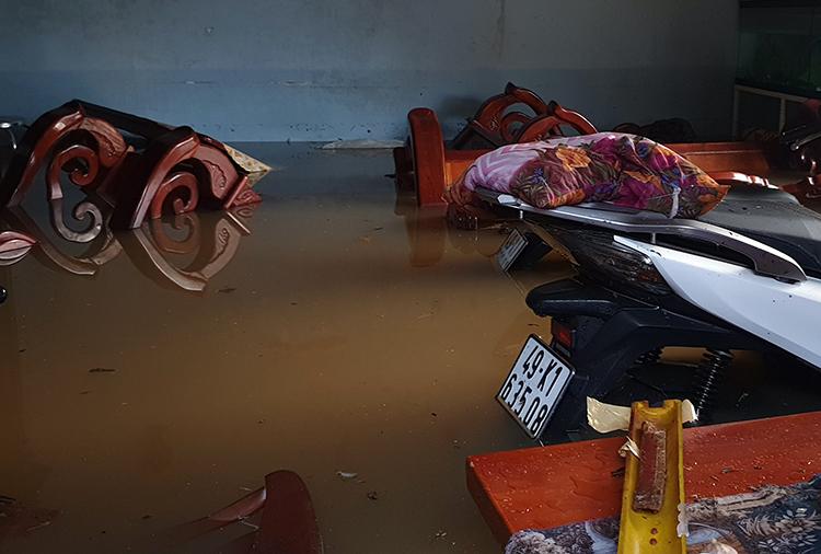 Nước tràn vào nhàngười dân trên đường Lê Văn Tám. Ảnh: Hoài Thanh.