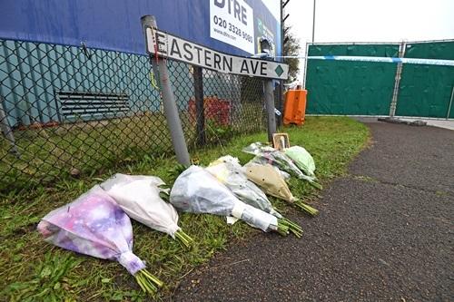 Người dân Anh hôm 25/10 đặt hoa tưởng niệm tại khu công nghiệp Waterglade, nơi xe container chở 39 nạn nhân được phát hiện. Ảnh: Reuters.
