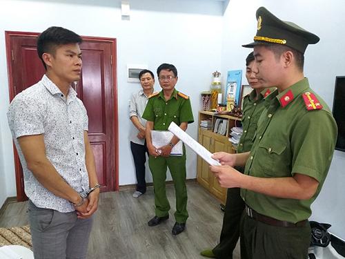Bị cáo Lợi (áo trắng, bên trái) thời điểm bị cảnh sát đọc lệnh bắt. Ảnh: C.A