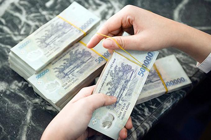 Nhân viên tại một ngân hàng kiểm đếm tiền trước khi cho vay. Ảnh. Anh Tú