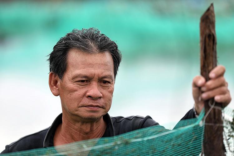 Ông Nguyễn Thanh Hóa thẫnthờ sau khi số cá mú đầu tư 150 triệu đồng mất sạch sau bão. Ảnh: Hữu Khoa.