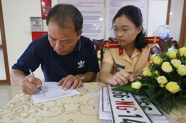 Một tài xế làm thủ thủ tục hành chính liên quan đến việc cấp đổi biển số xe ở trụ sở Cục CSGT. Ảnh. Bá Đô