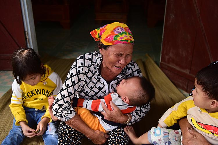 Bà Cao Thị Uyên bên 3 đứa cháu nội là con của anh Thành. Ảnh: Giang Huy.