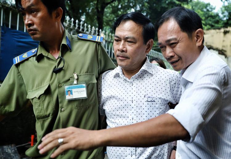 Ông Nguyễn Hữu Linh được nhân viên bảo vệ tòa che chắn. Ảnh: Hữu Khoa.