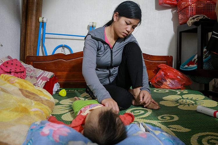 Chị Thái Thị Giang (huyện Diễn Châu, Nghệ An) bên con trai 11 tháng tuổi, vừa ngóng tin chồng – anh Cao Huy Thành mất tích tại Anh. Ảnh: Nguyễn Hải.