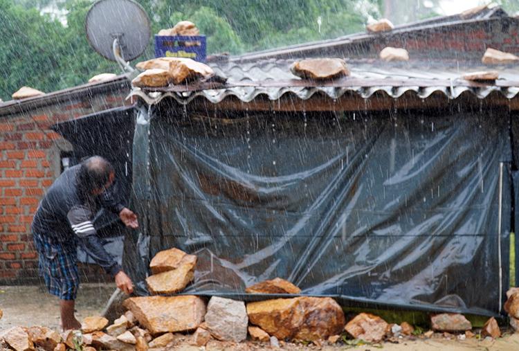 Ông Trần Út, người dân xã Xuân Cảnh (thị xã Sông Cầu) đội mưa ra ghè đá lại căn nhà gần biển. Ảnh: Việt Quốc.