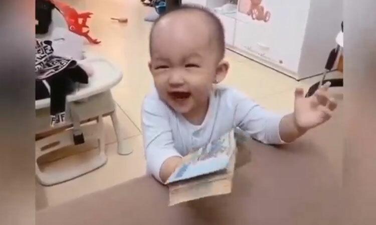 Em bé đang khóc bỗng im bặt khi thấy cọc tiền -