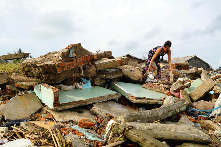 Bà Nguyễn Thị Loan đang bới tìm phế liệu từ hai căn nhà đã đổ sập của hàng xóm. Ảnh: Hoàng Nam.
