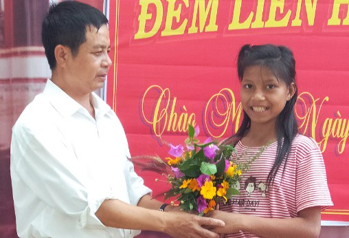 Thầy Trần Mạnh Thùy, Hiệu trưởng trường THCS Đăk Rơ Ông, nhận bó hoa rừng học sinh tặng nhân ngày Nhà giáo. Ảnh: Thầy Thùy cung cấp.